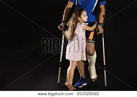 A little girl abracing man with crutches and plaster cast