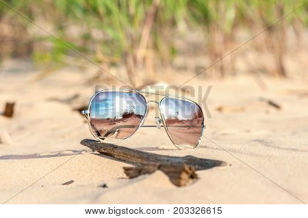 Trendy sunglasses with reflection lost on the beach sand. Outdoors closeup.