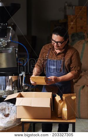Smiling roastry owner putting packed coffee into cardboard box