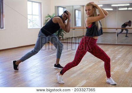 Full length of dancers rehearsing against mirror on wooden floor at studio