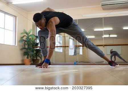Full length of male dancer rehearsing on wooden floor at studio