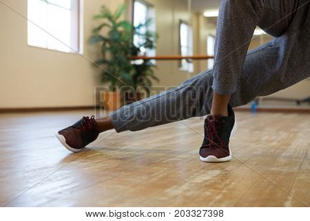 Low section of male dancer rehearsing on wooden floor at studio