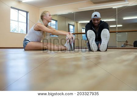Full length of dancers stretching against mirror on floor at studio