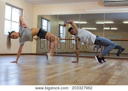 Full length of dancers rehearsing against mirror on floor at studio