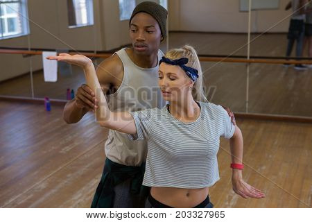 Young man assisting female friend in dance against mirror at studio