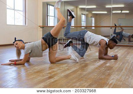 Side view full length of friends rehearsing dance on floor at studio