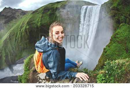Cheerfull Girl in waterproof clothing sits on the cliff on background of Skogafoss waterfall in Iceland. View from above