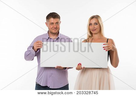 Young glad couple portrait of a confident businessman showing presentation, pointing paper placard gray background. Ideal for banners, registration forms, presentation, landings, presenting concept.