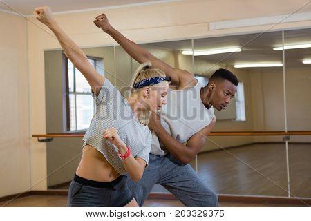 Friends rehearsing dance against mirror against mirror at studio