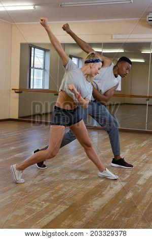 Full length of friends rehearsing dance against mirror on floor at studio