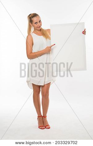 Young glad woman portrait of a confident businesswoman showing presentation, pointing placard gray background. Ideal for banners, registration forms, presentation, landings, presenting concept.