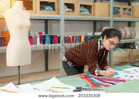 Smiling Pretty Designer Woman Holding Blue Zipper