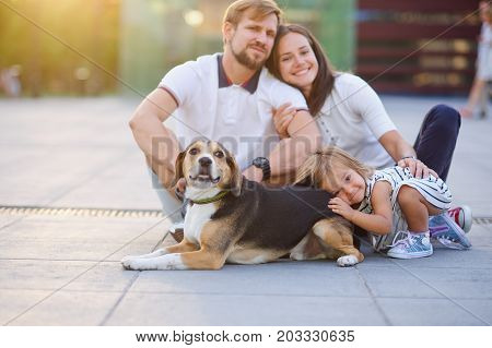 Wonderful young family is resting sitting on the ground. Dad Mom little daughter and beagle. Warm summer weather good mood.