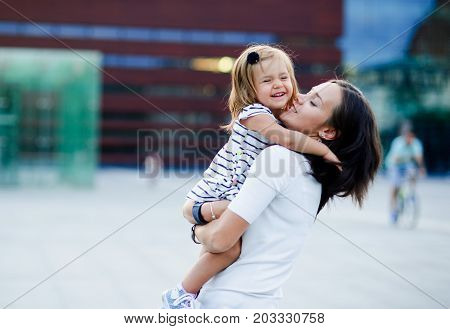 The young woman holds the little daughter on hands.