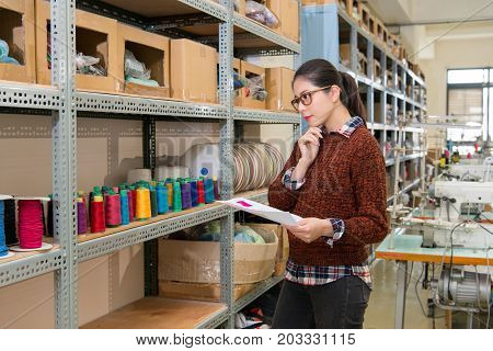 Tailor Standing In Front Of Color Spool Thread