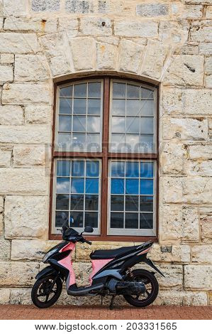 Black and Pink Scooter against a Stone Wall in Bermuda