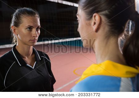 Female volleyball players looking each other while standing at court