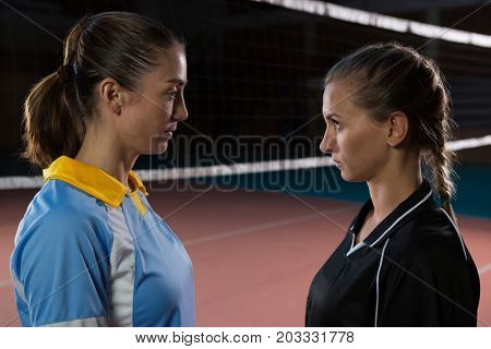 Side view of female volleyball players looking each other while standing at court
