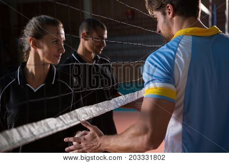 Volleyball players giving handshake through net at court