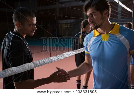Volleyball players shaking hands through net at court
