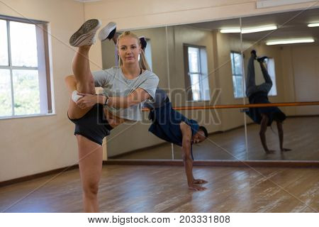 Portrait of female dancer with friend rehearsing at studio