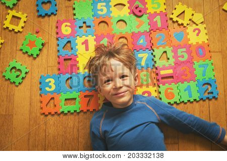 happy little boy playing with puzzle, education and learning