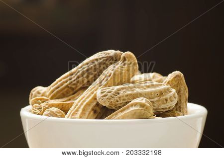 Boiled peanuts or groundnuts in a bowl on black background