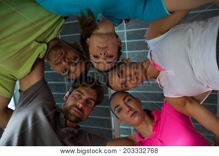 Low angle portrait of volleyball players huddling at court