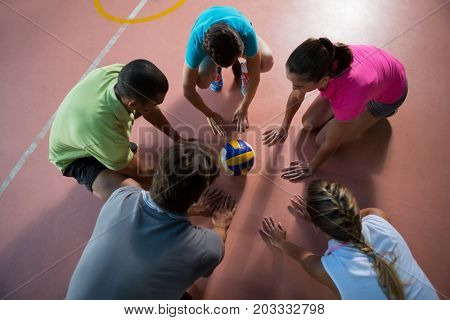 High angle view of players planning strategy while looking at volleyball