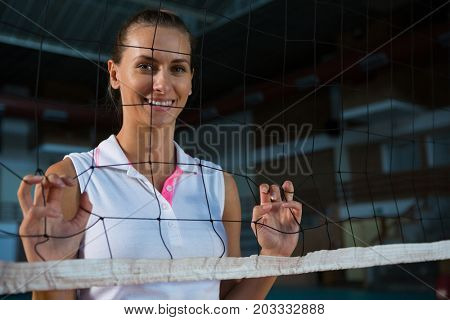 Portrait of smiling female volleyball player standing behind net at court