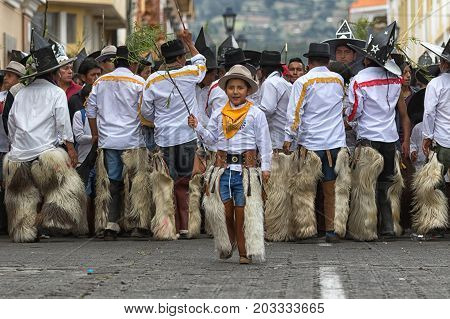June 29 2017 Cotacachi Ecuador: indigenous kichwa boy wearing furry chaps is dancing at Inti Raymi celebration