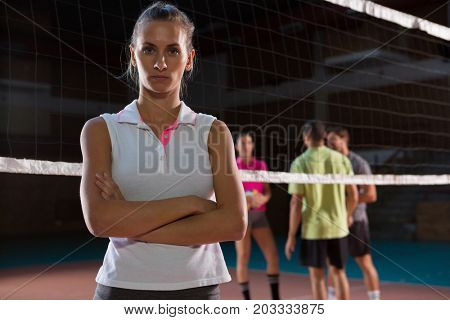 Portrait of confident female volleyball player with teammates in background at court