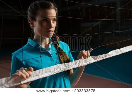 Thoughtful female volleyball player by net looking away in court
