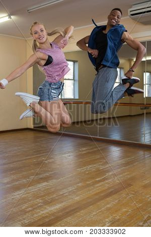 Full length portrait of dancers jumping at hardwood floor in studio
