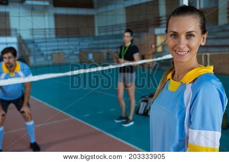 Portrait of smiling female volleyball player standing at court