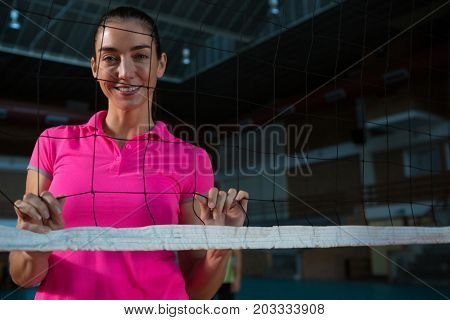 Portrait of smiling female volleyball player standing behind net