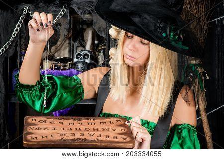 Concentrated Blond Witch With A Ouija Board And Crystal Wonders