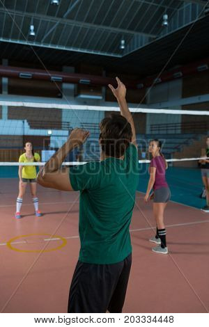 Rear view of male player with team practicing volleyball at court