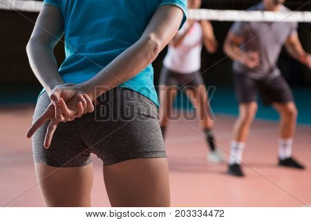 Mid section of female player gesturing at volleyball court
