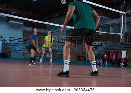 Full length of players practicing volleyball at court