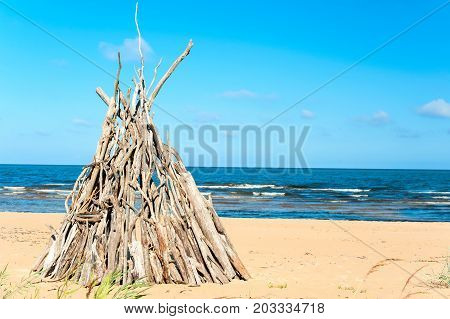 Wigwam Made from wooden branches on the sand of baltic sea beach. Multicolored summertimee outdoors.