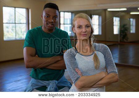 Portrait of confident young dancers standing on floor in studio
