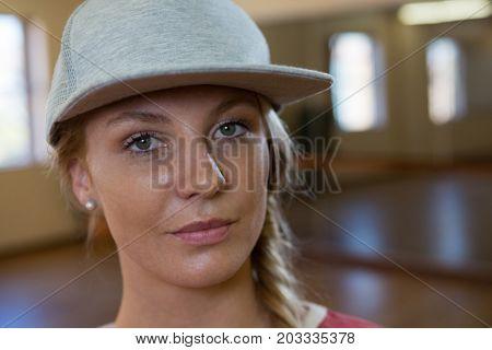 Close-up portrait of female dancer wearing cap in studio
