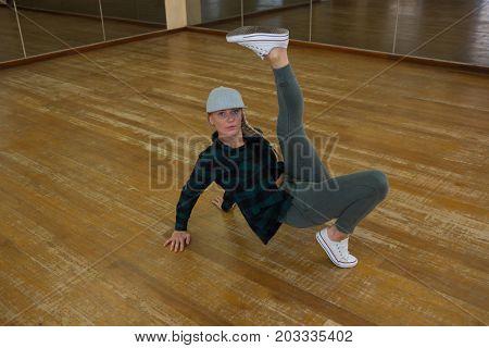 Full length portrait of woman rehearsing dance on wooden floor in studio