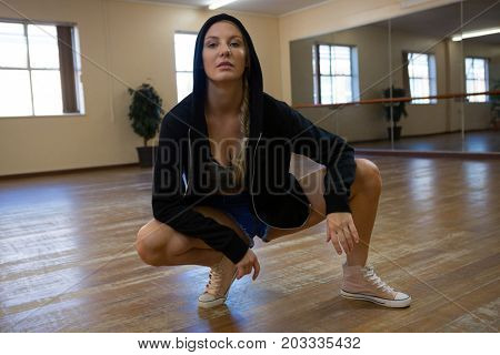 Full length portrait of young woman rehearsing dance on floor in studio