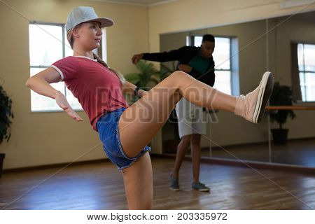 Full length of female dancer with friend practicing on floor in studio