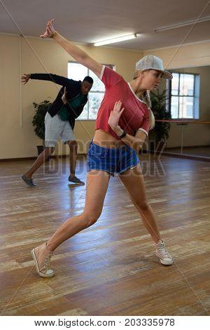 Full length of young dancers practicing on wooden floor in studio