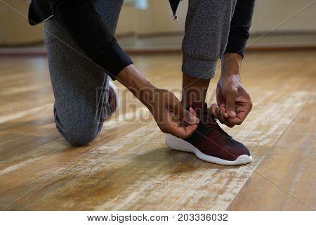 Low section of dancer tying shoelace on wooden floor in studio