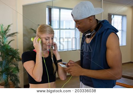 Woman with headphones connected to phone held by male friend in dance studio