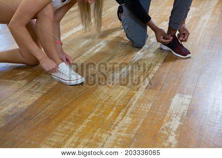 Low section of dancers tying shoelaces on wooden floor in studio
